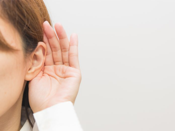An ear with a hand cupped against it