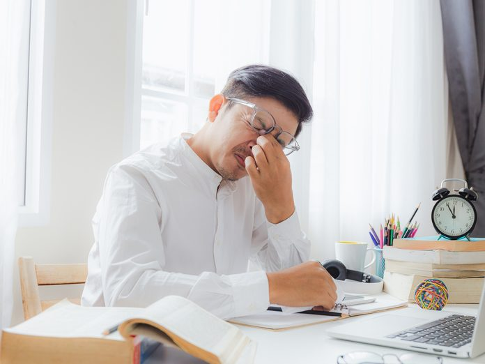 Man at a desk holding his face in his hand