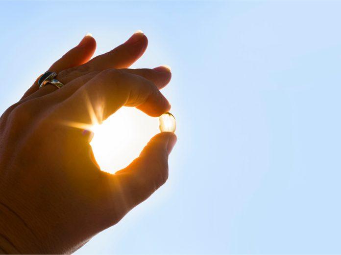 Vitamin D capsule in front of sun