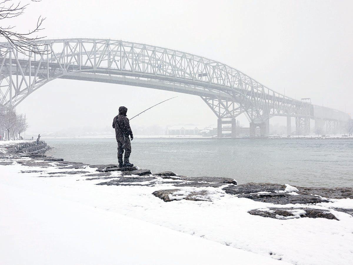 Man fishing on Blue Water Bridge joining Point Edward Ont