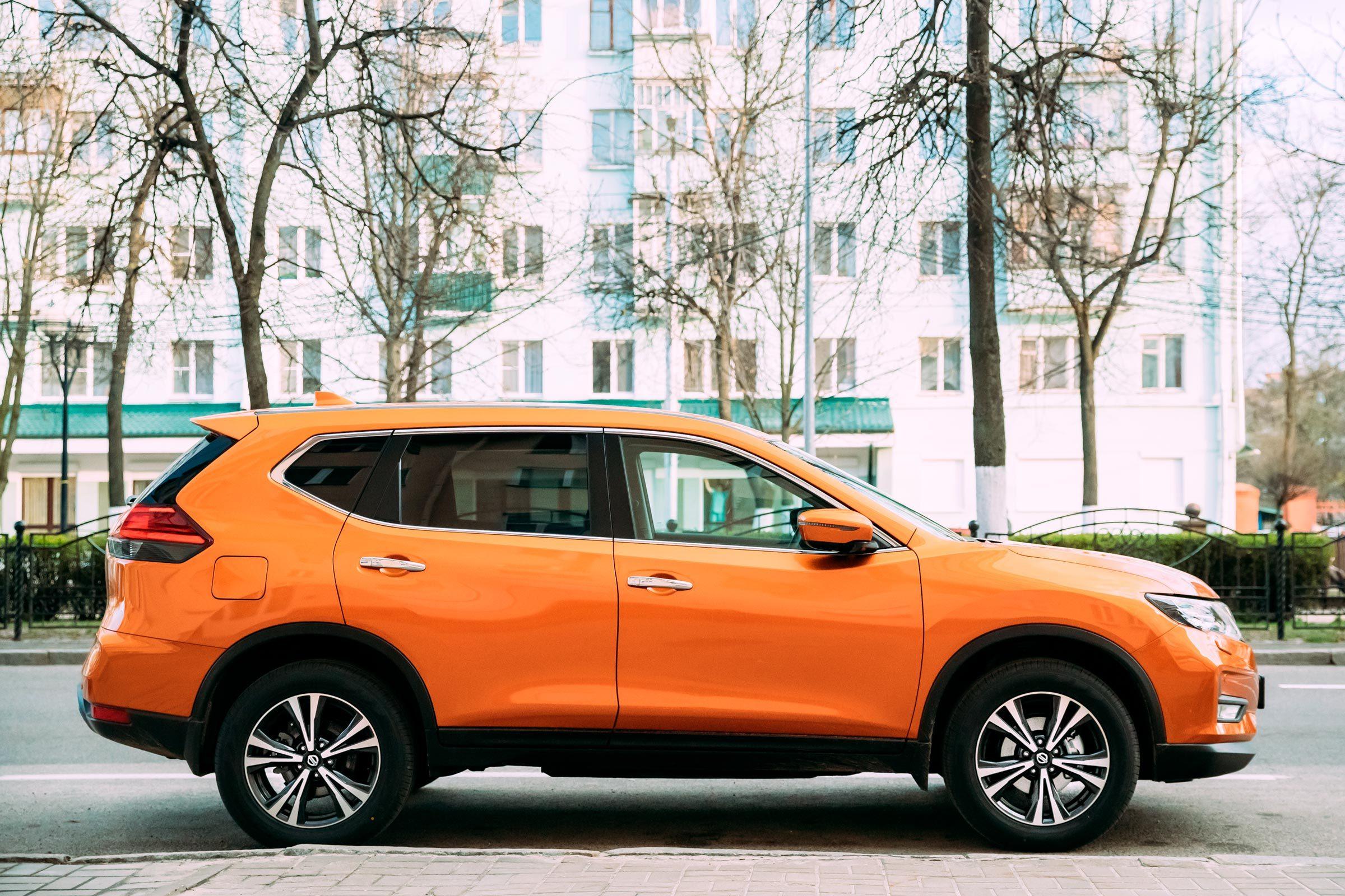 Orange Nissan X-Trail third generation Car Parked At Street. Side View