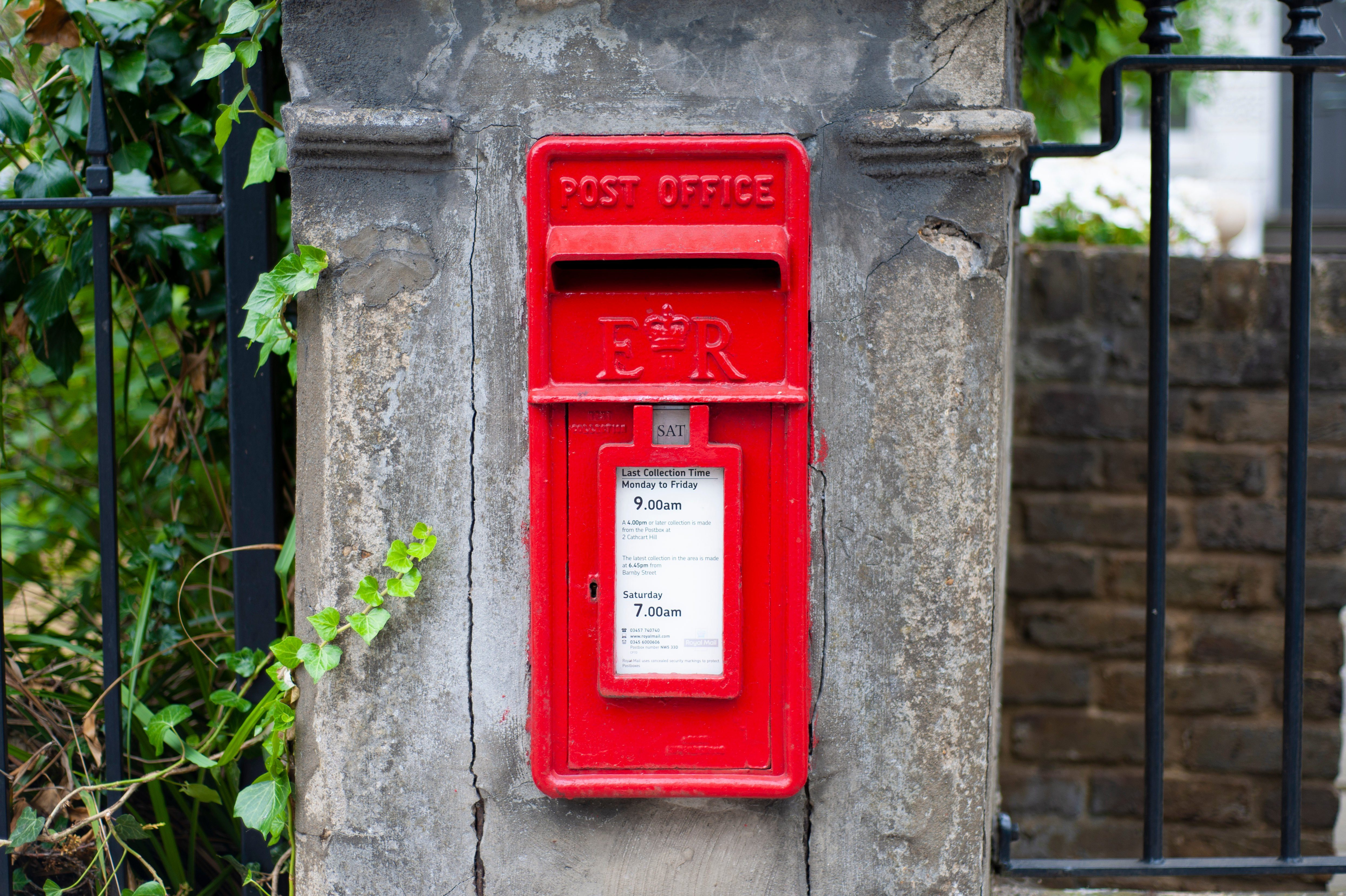 London - United Kingdom - 20 July 2018 - Traditional old English red postbox mounted in a cotswold stone wall.