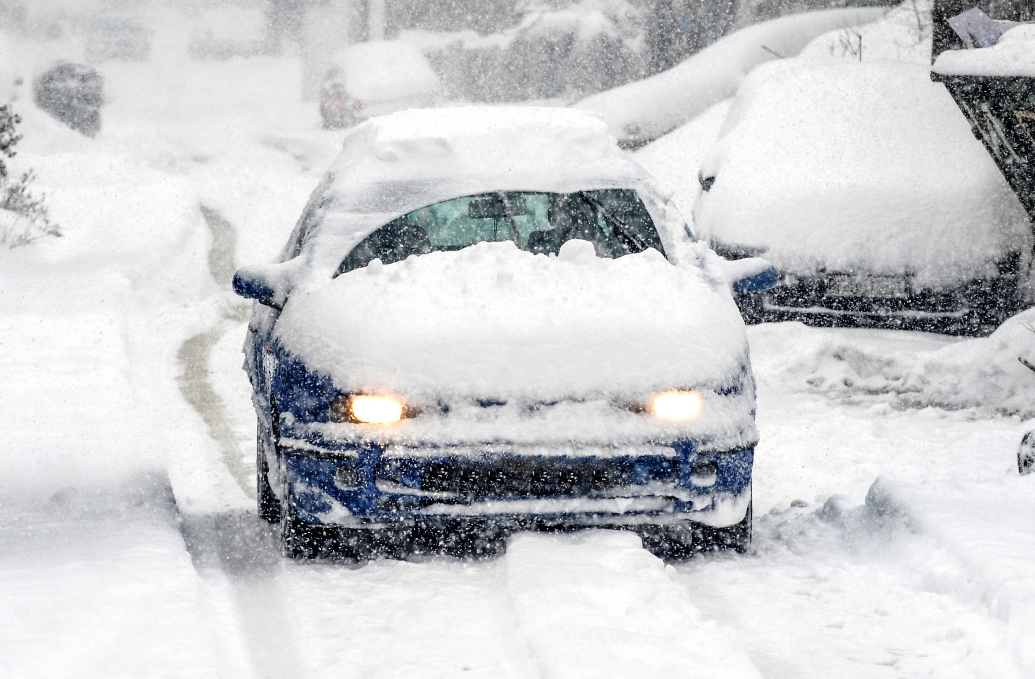 A snow covered car drives in winter storm