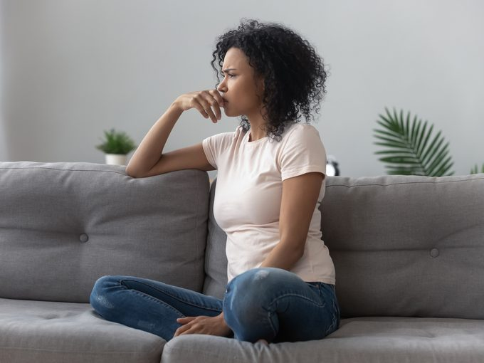 Woman sitting on couch looking concerned