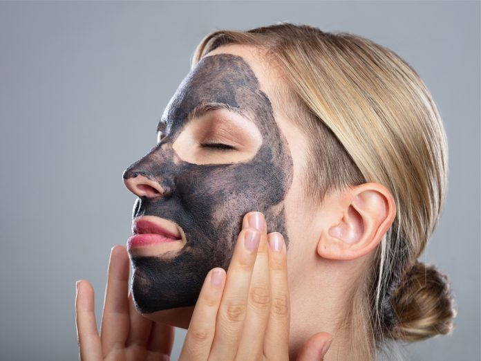 Woman putting on activated charcoal face mask