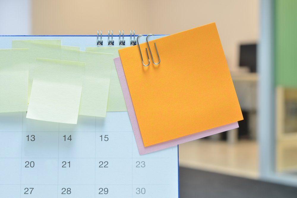 Paper notes on calendar at business office with copy space for text,office supplies