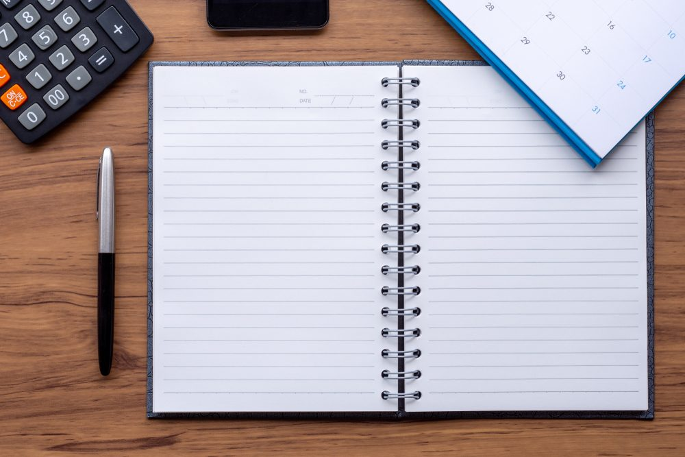 White notebook, calculator, pen, calendar and phone isolated on wooden background.