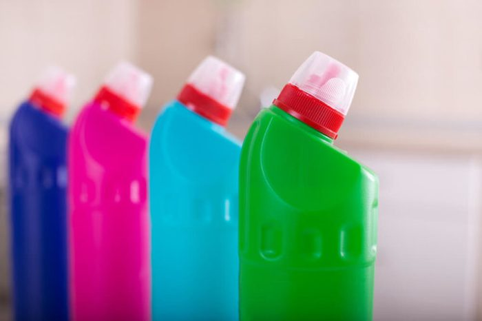 Close up of group of colorful cleaning supplies with tiled wall in background. House keeping and hygiene concept