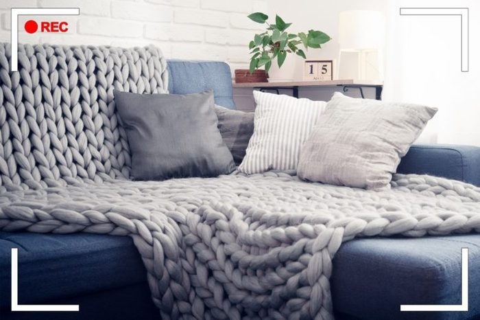 couch with blanket and pillows near a window.