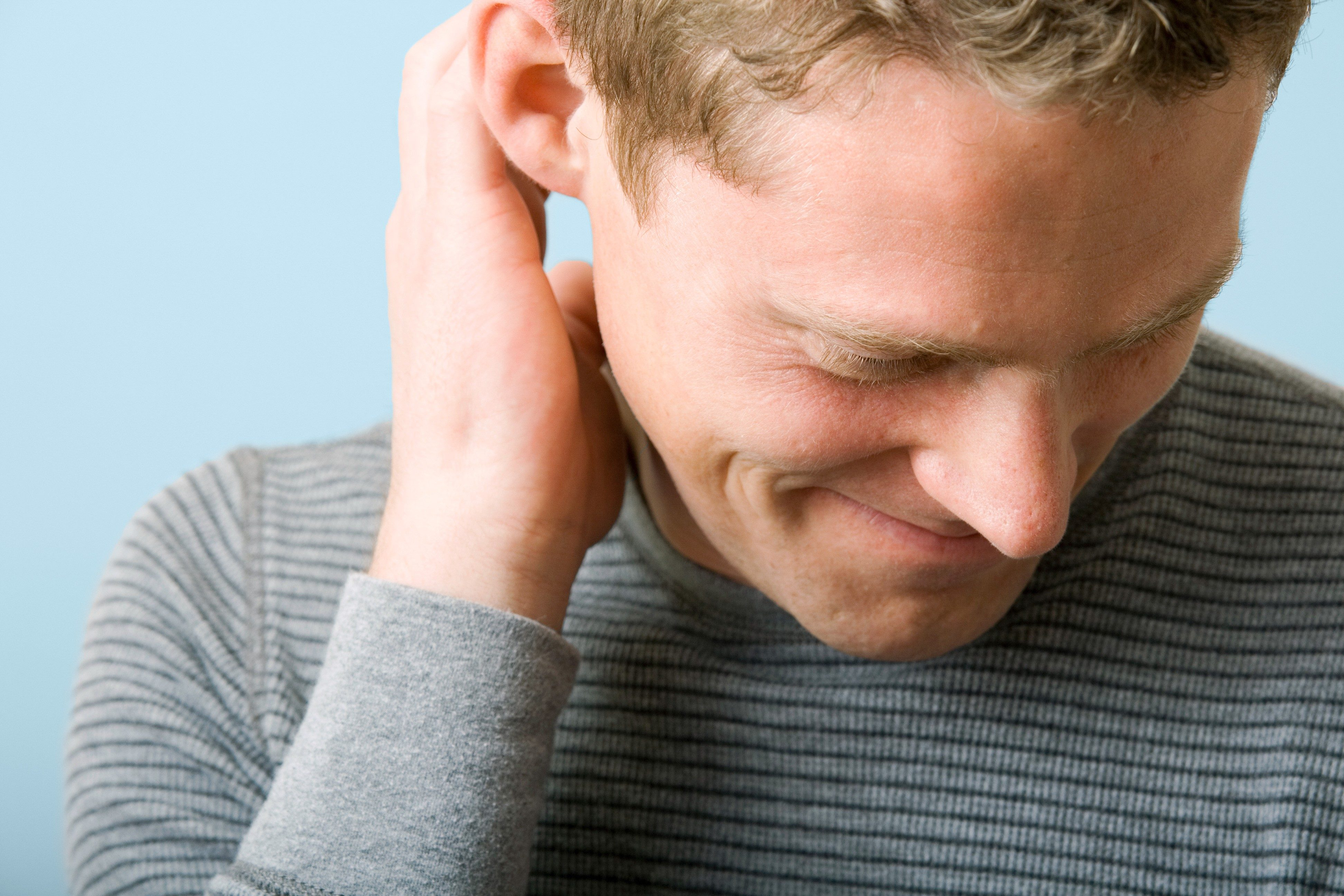 portrait of a man scratching his ear looking down. blue-gray background