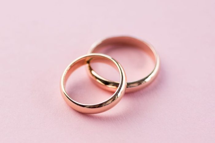 Close-up view of shiny golden wedding rings on pink background