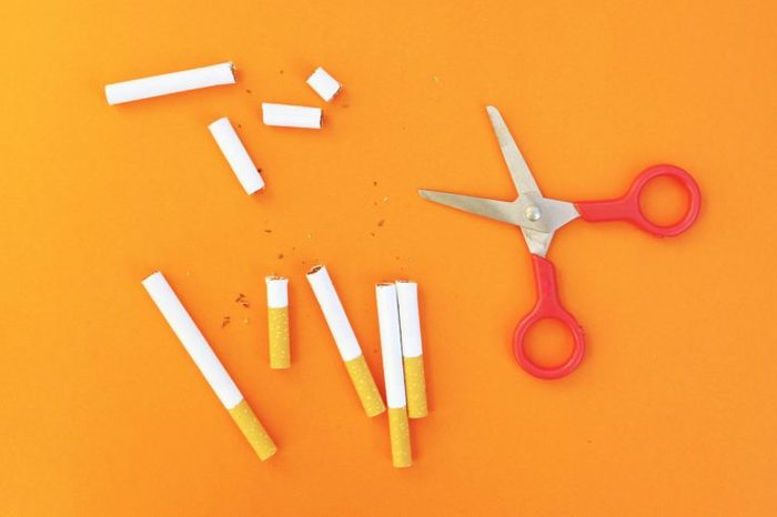 cut cigarettes and red scissors on orange background