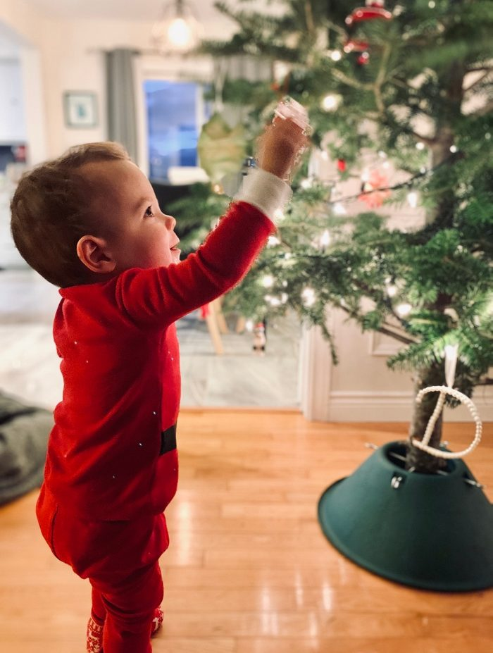 Small boy putting a decoration on a tree