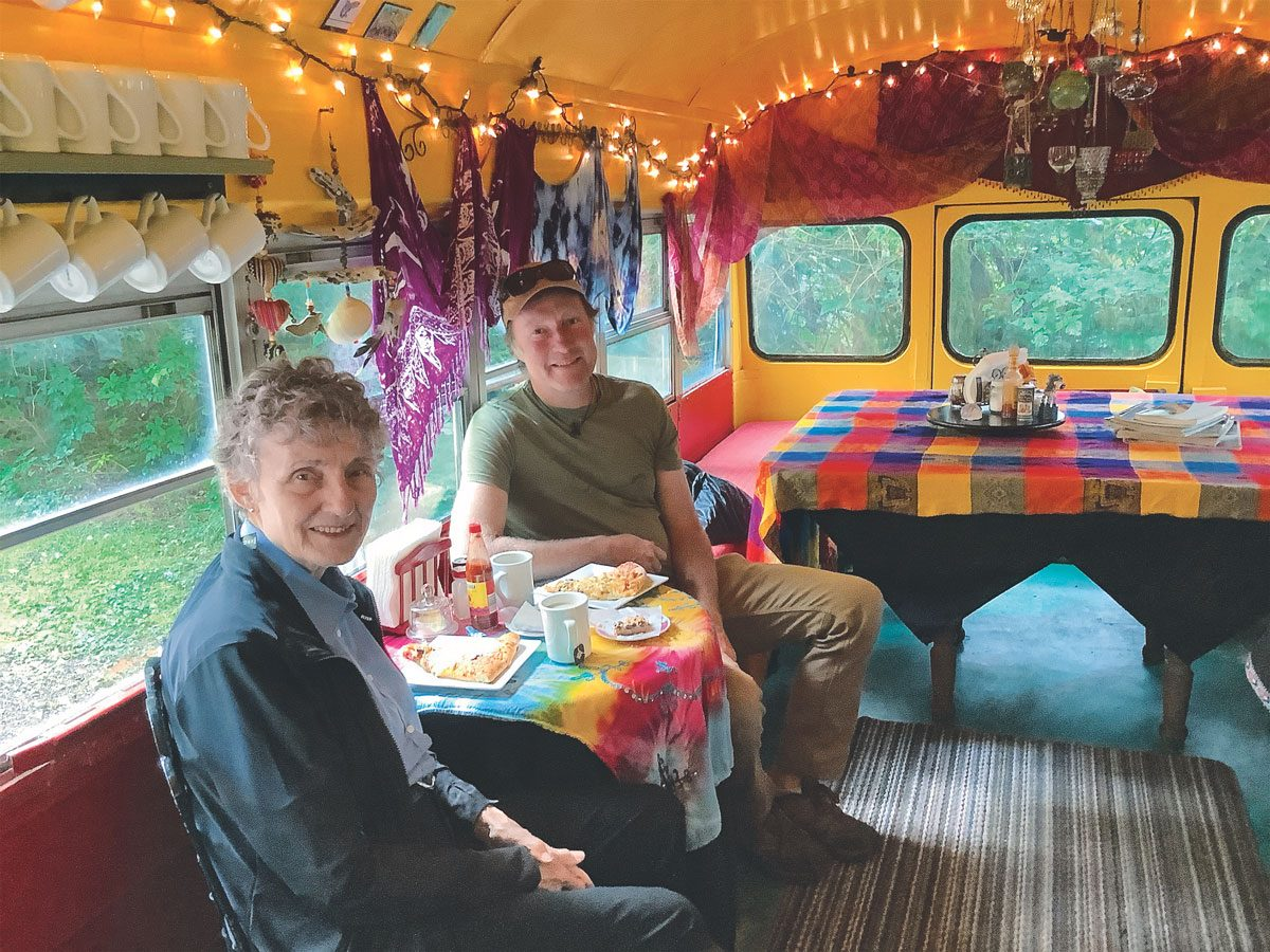 Penny and Brett enjoying coffee and treats at the Moon Over Naikoon Bakery—a converted school bus parked off the road in the woods