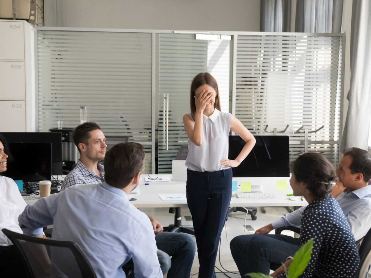 Female employee feeling awkward after receiving compliments from co-workers