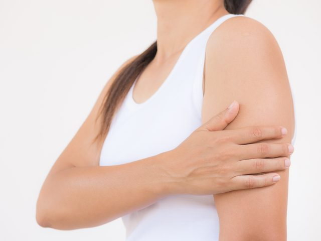 Woman clutching left arm