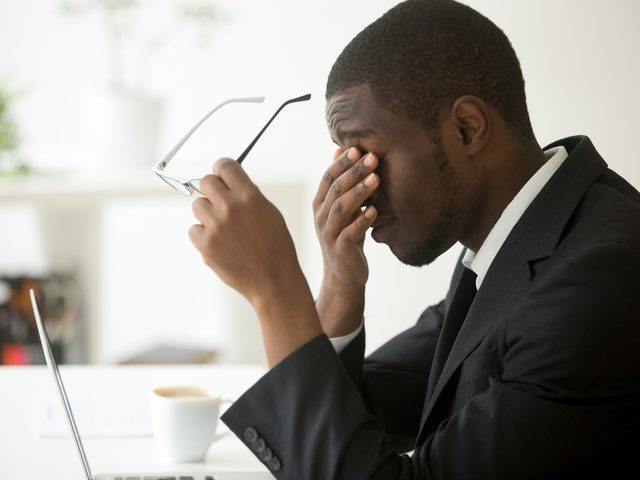 Man sleepy at desk with hand to face