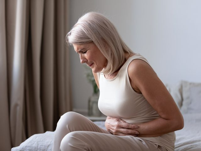 Woman holding stomach in pain