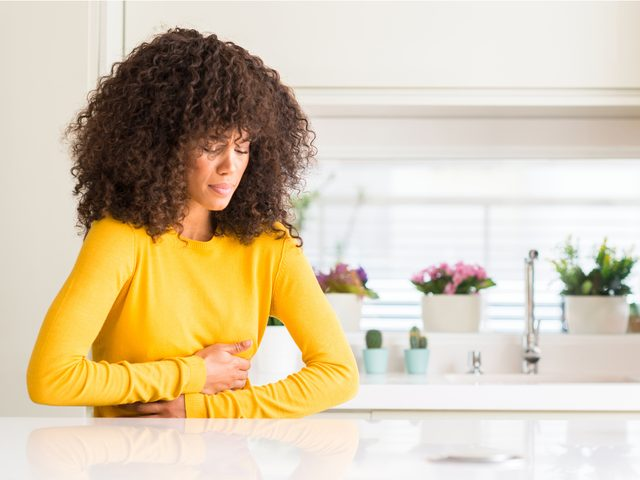 Woman in kitchen holding stomach