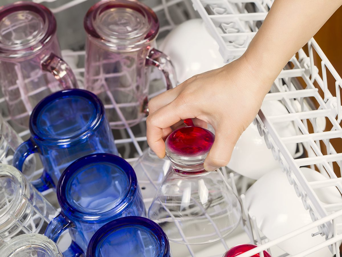 Horizontal photo of female hand putting in glassware to be washed by dishwasher with blue, red, clear, pink glasses and white bowls in background