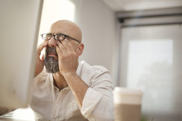 Signs you need new glasses - Senior businessman rubbing his tired eyes