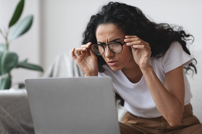 Signs you need new glasses - lady holding her glasses and squinting, looking at laptop screen, having vision troubles