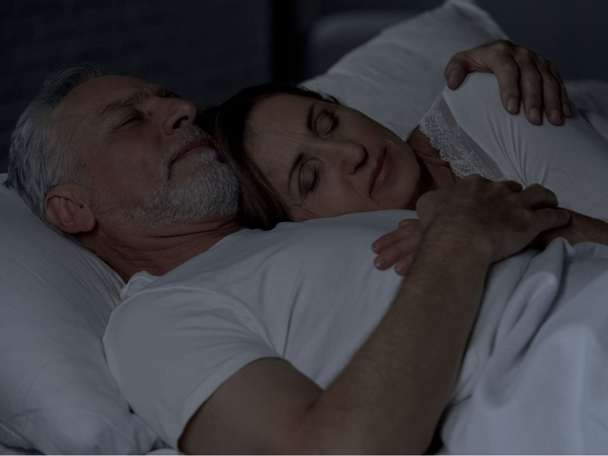 Elderly couple sleeping in bed together