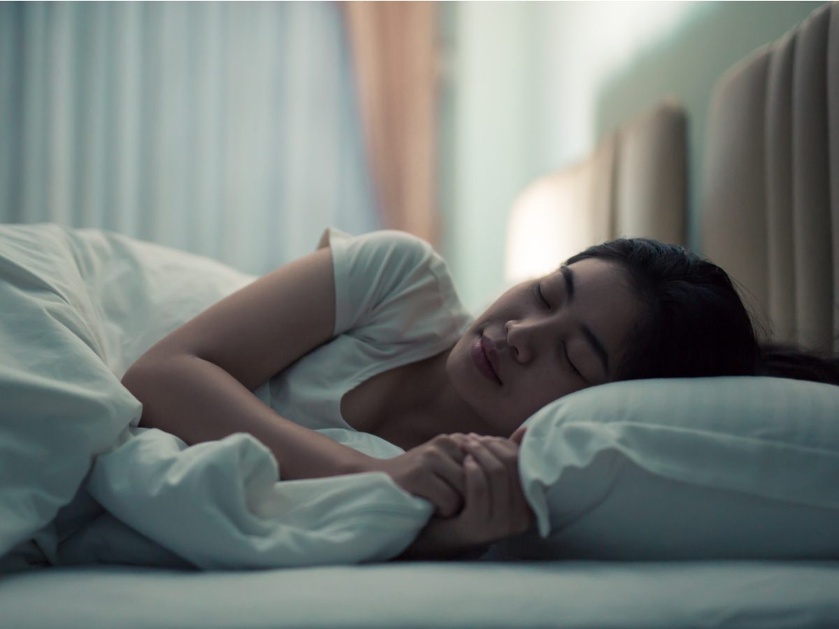 Asian woman sleeping in bed with her lamp on