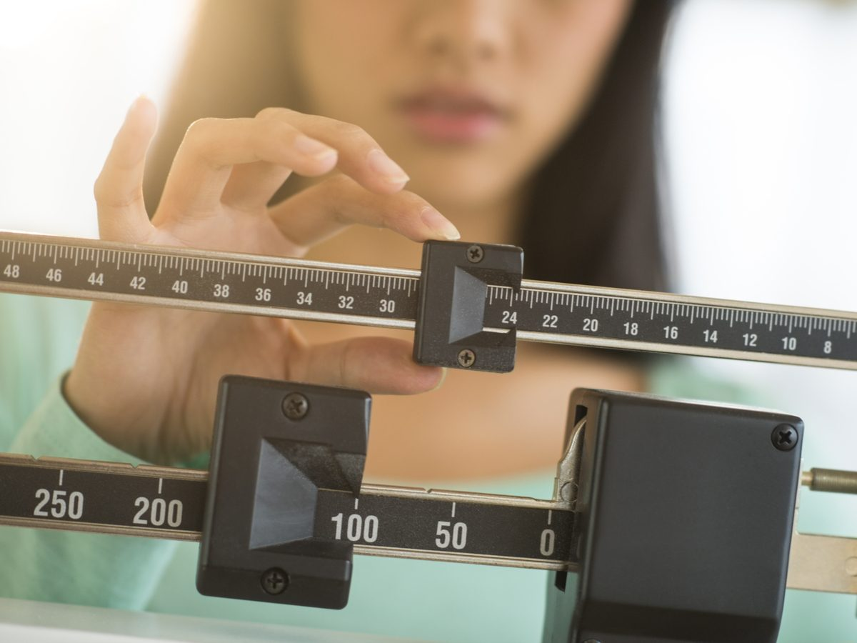 Woman using weight scale