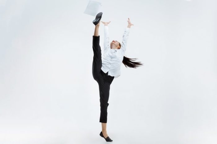 Happy business woman dancing and smiling isolated on white.