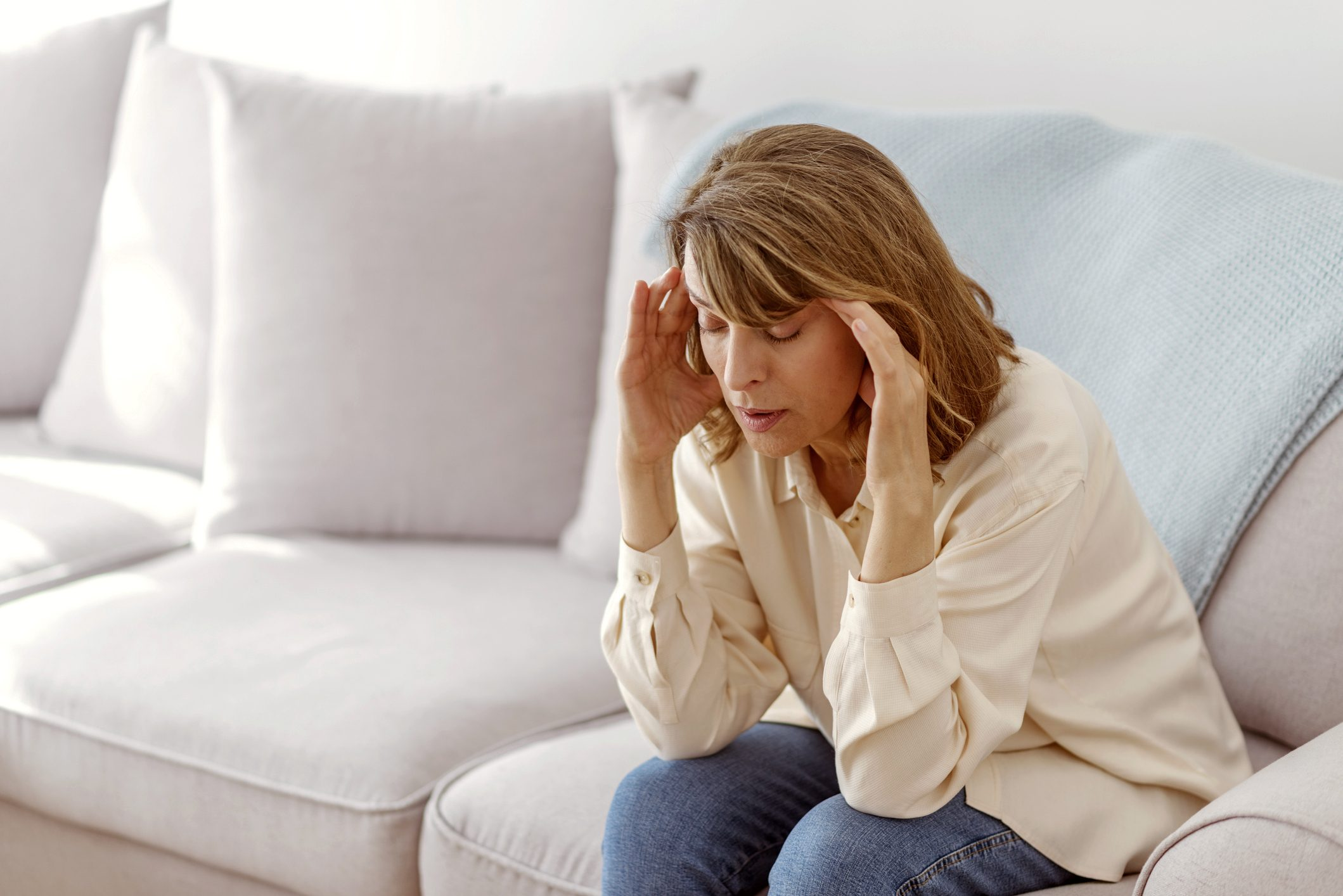 woman sitting on couch with headache pain