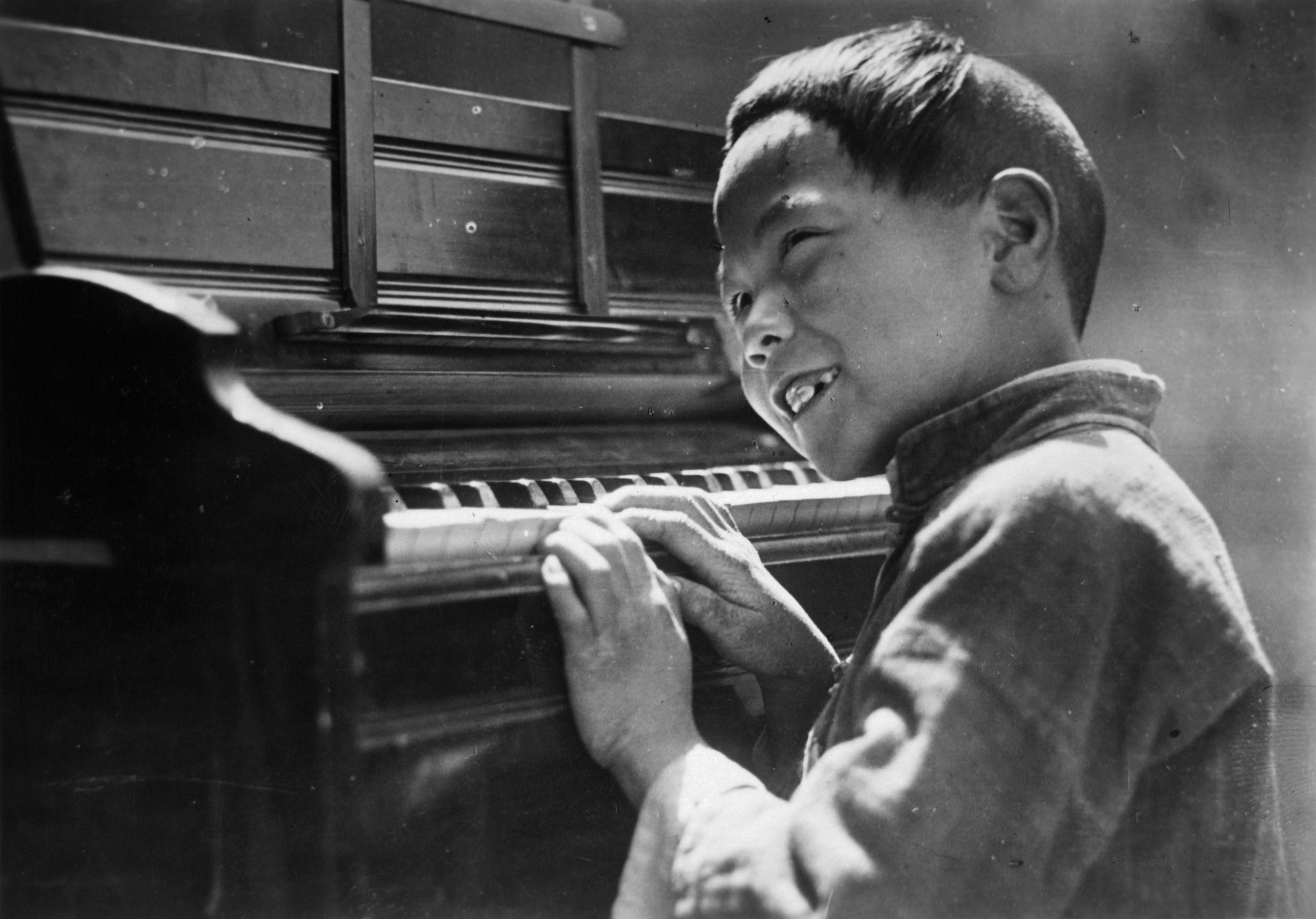A happy Chinese boy practices his Easter Alleluias on the missionary's piano in Loyang , China.
