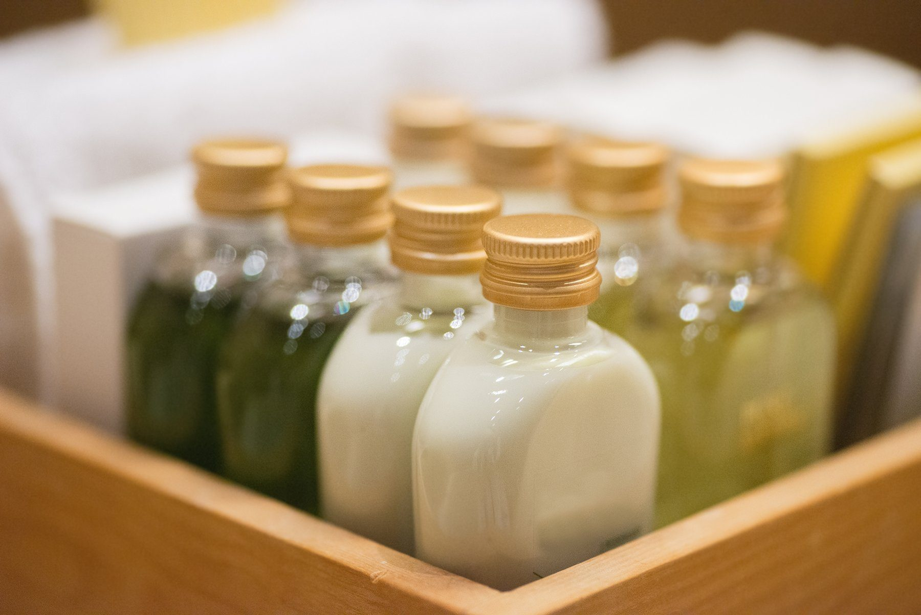 small shampoo bottles in wodden basket in hotel room