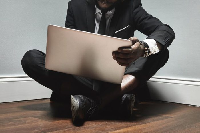 business man sitting on the floor in the corner with laptop