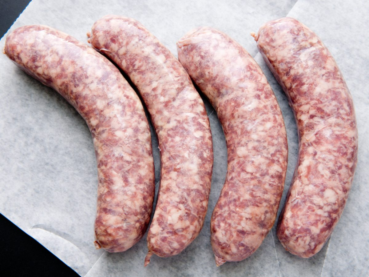 Four uncooked sausages on paper