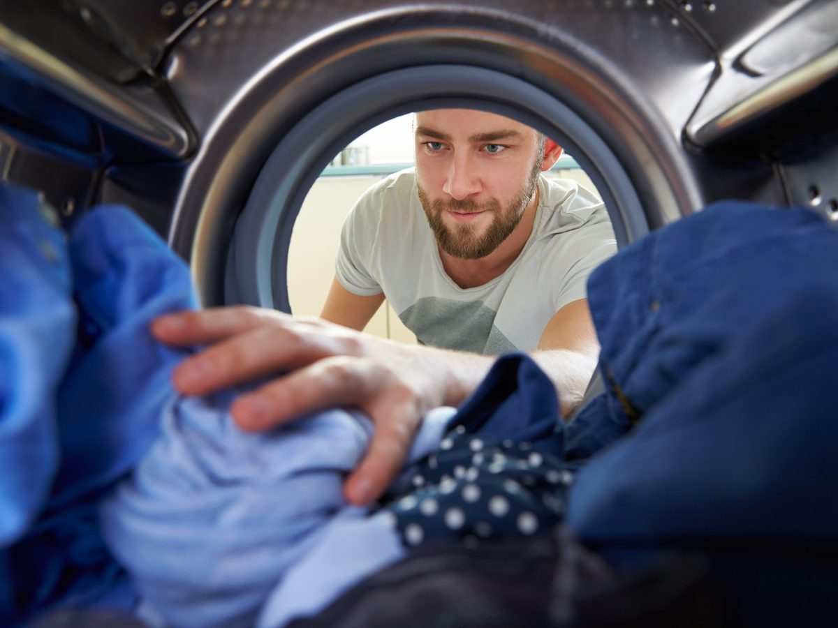 Man removing clothing from washing machine