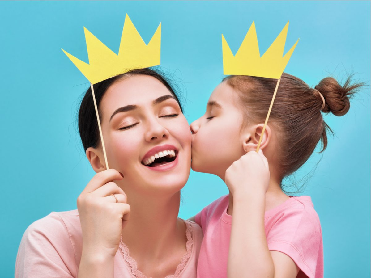 Daughter kissing mother while wearing paper crowns