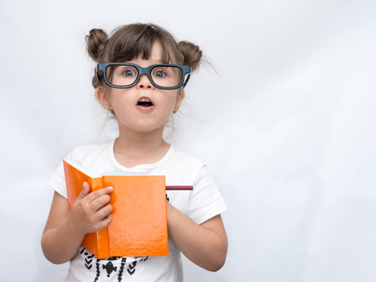 Funny little girl with fake glasses writing in a journal