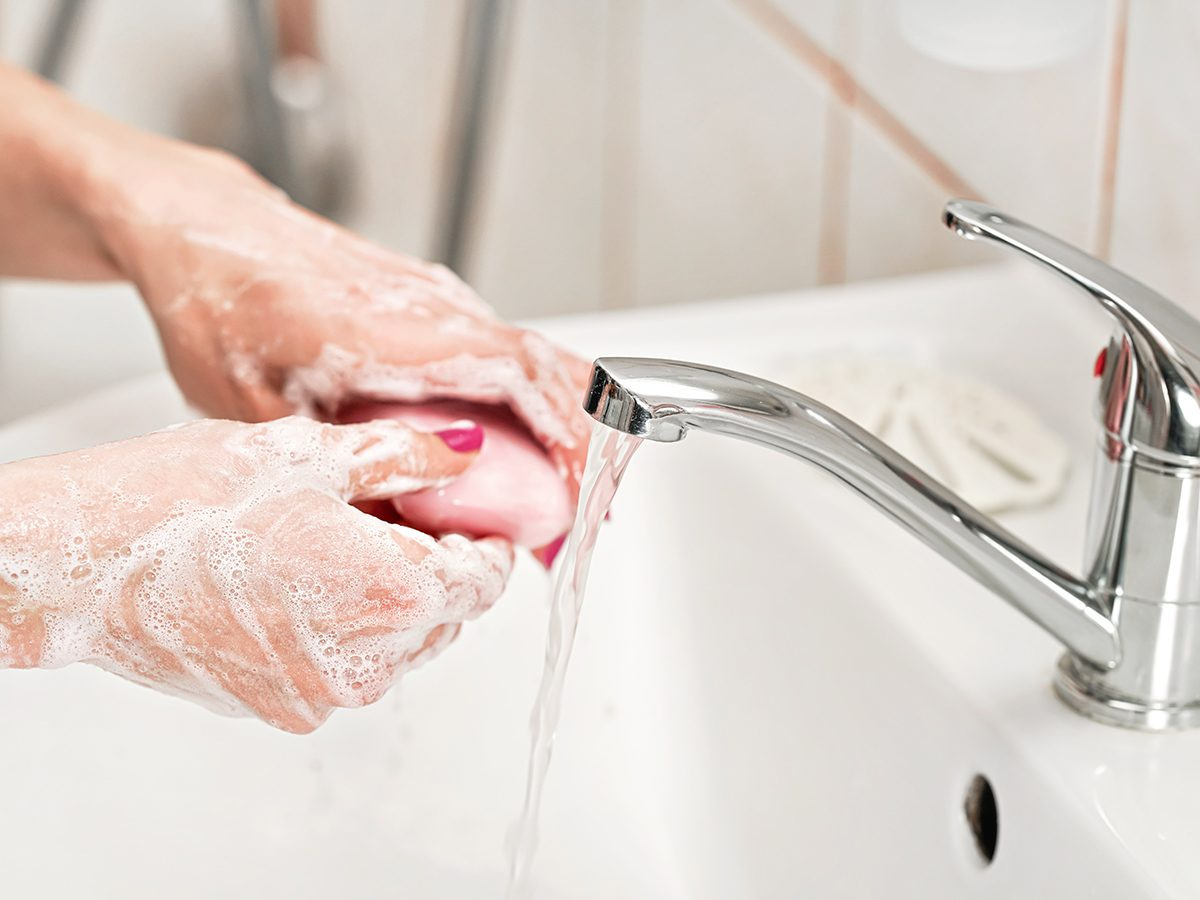 Person washing their hands under water tap faucet with pink soap bar. Detail on suds covered skin. Personal hygiene concept - coronavirus covid19 outbreak prevention