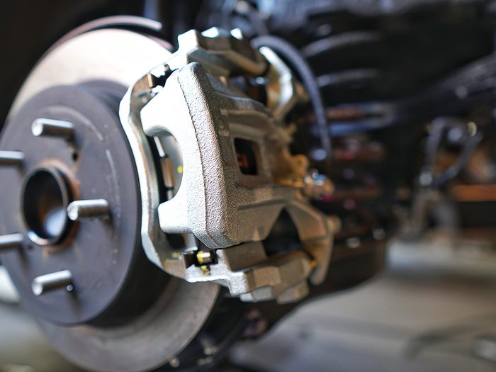What is a brake caliper - Selective focus of Brake Disc of the vehicle for repair.Automobile mechanic in process of new tire replacement.Car brake repairing in garage.Car Service and technician concept.