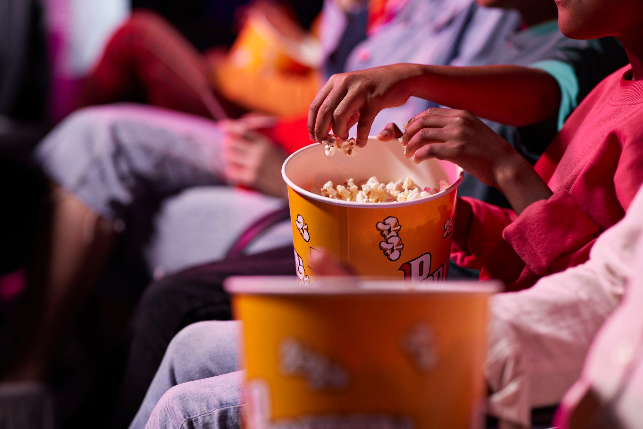 Midsection of friends sharing popcorn while sitting in theater