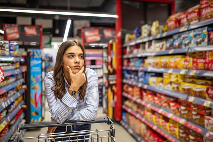 Woman buy products with her trolley at supermarket.