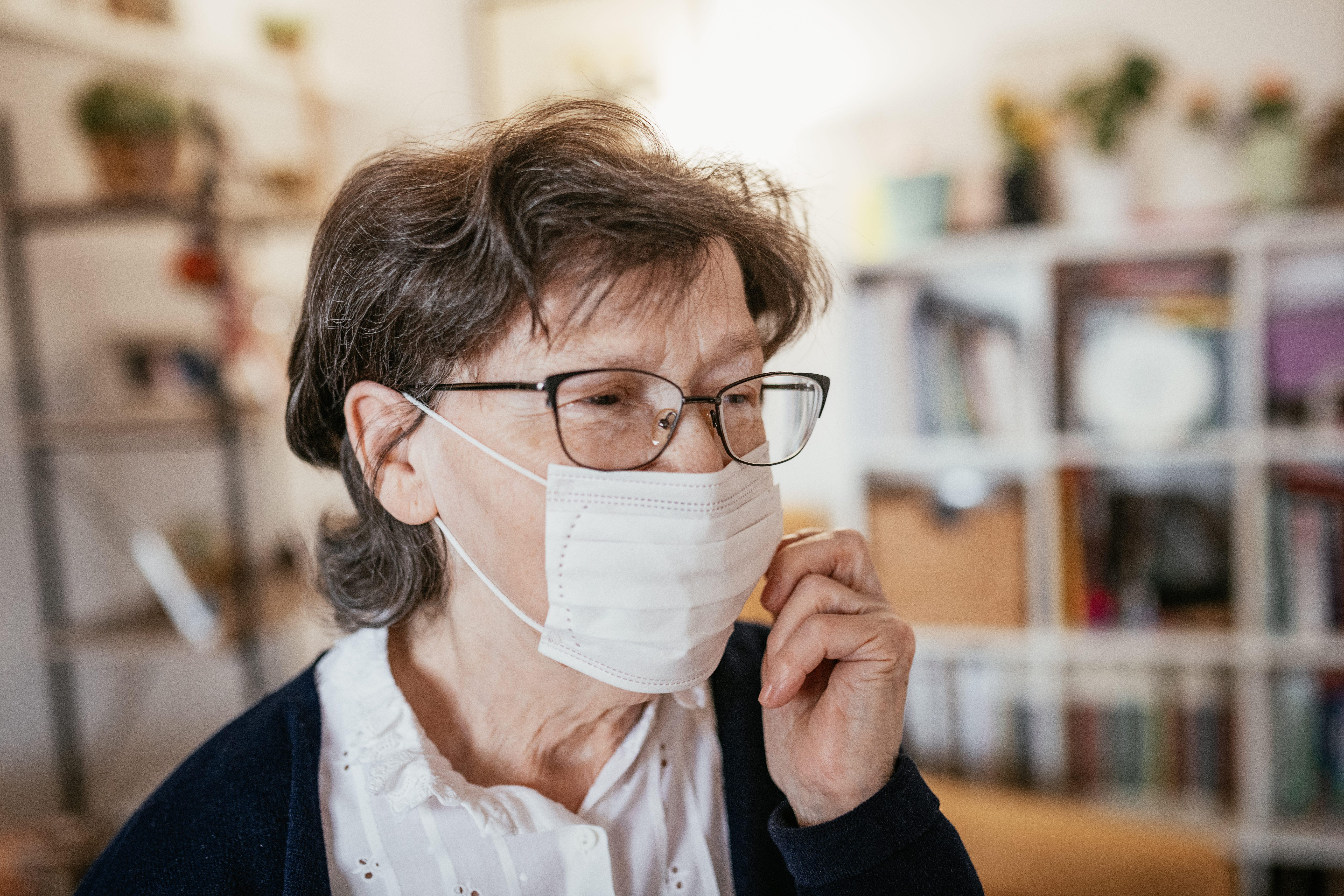 Senior woman with hygienic facial mask at home