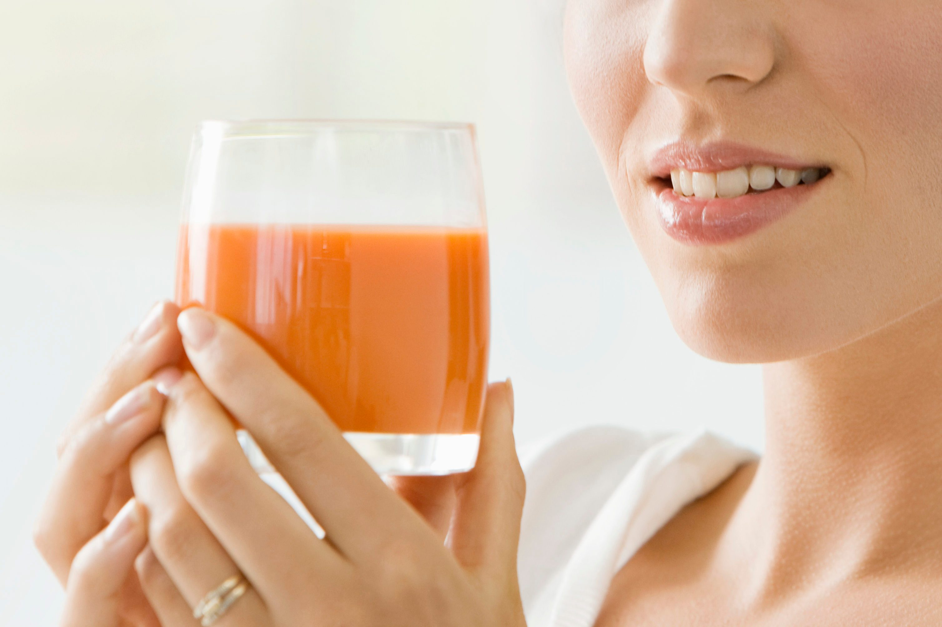 Woman holding a glass of tomato soup