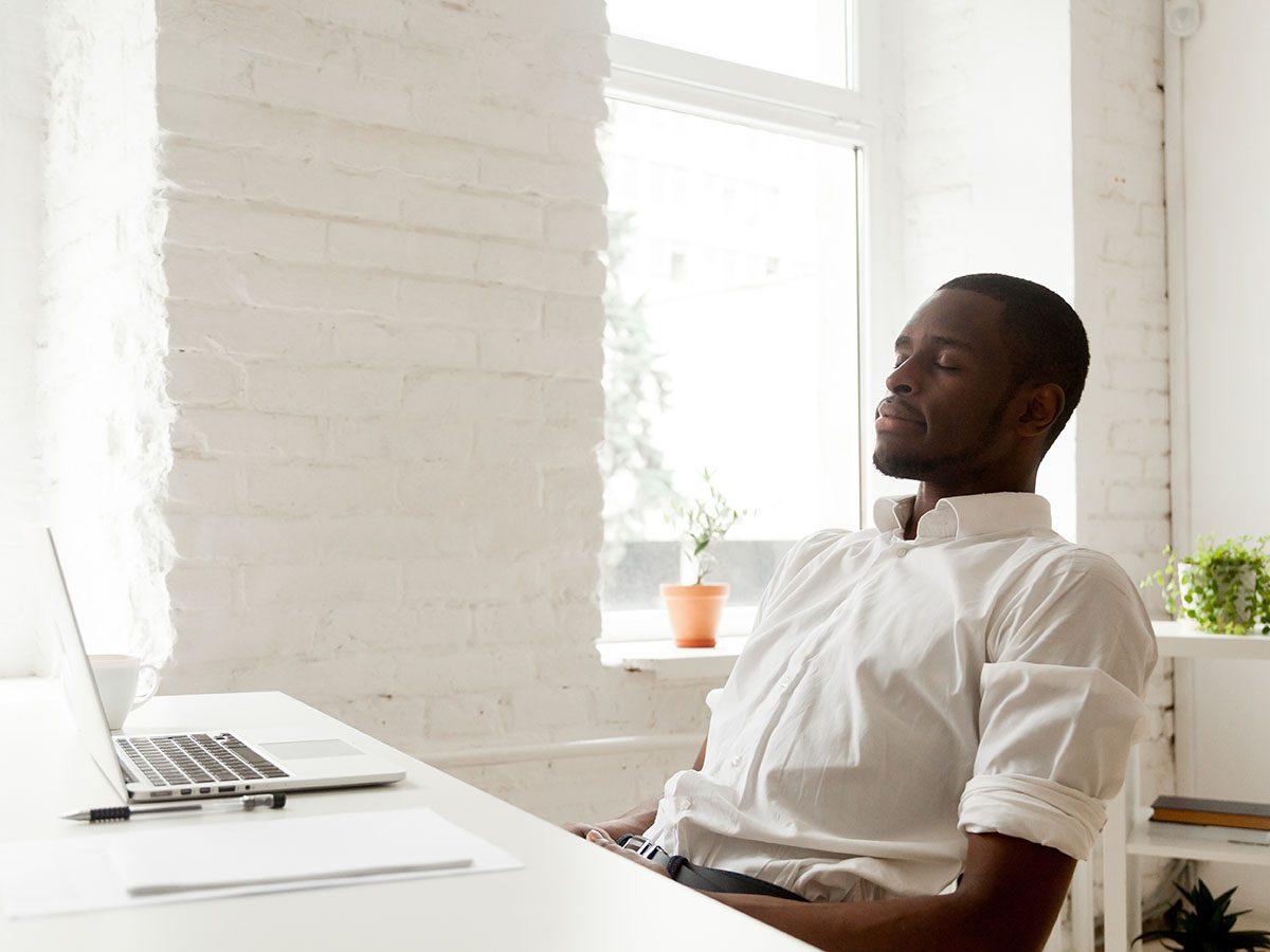 Man meditating on desk.