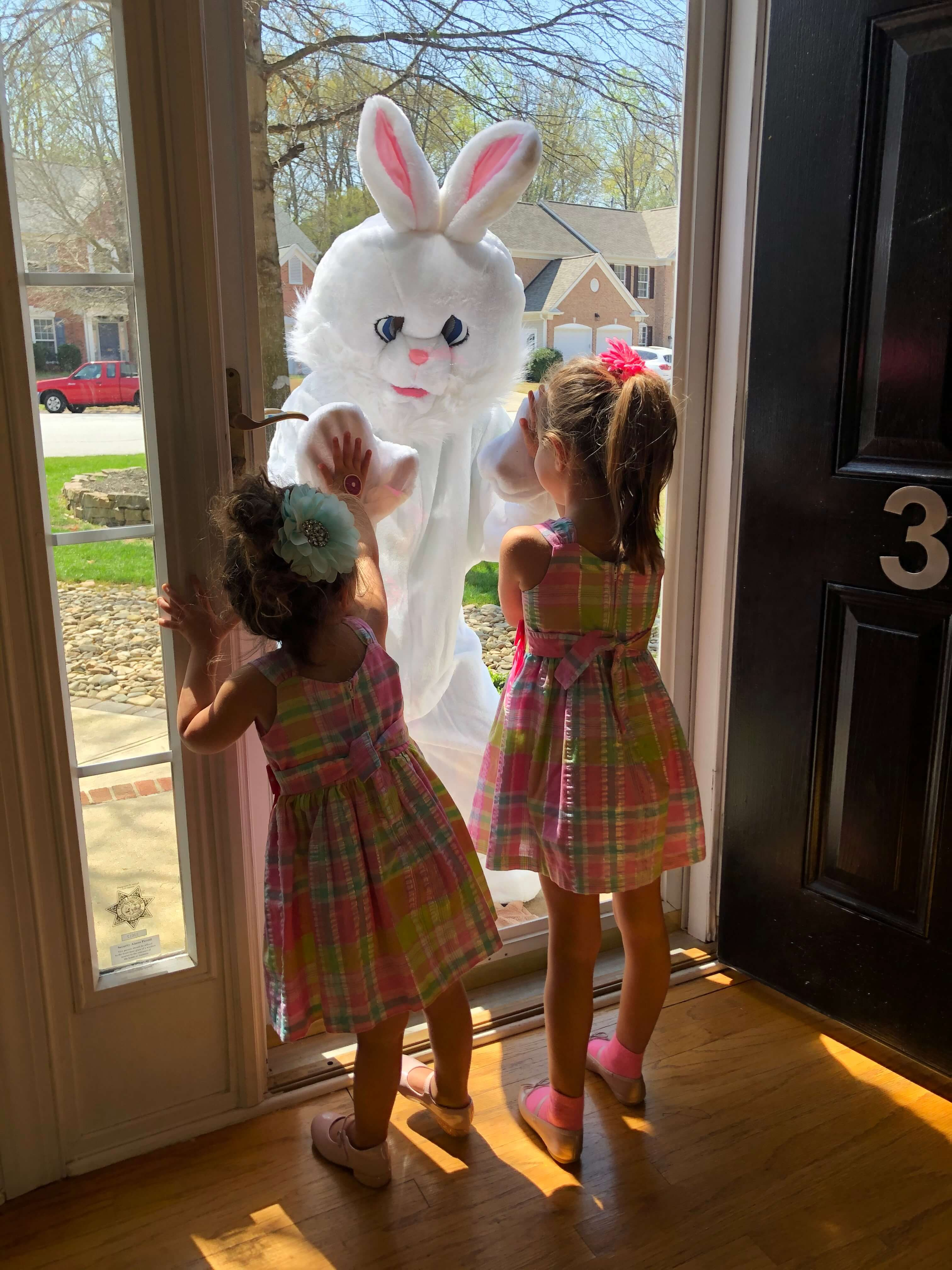 Easter bunny visiting two little girls at their home on Easter