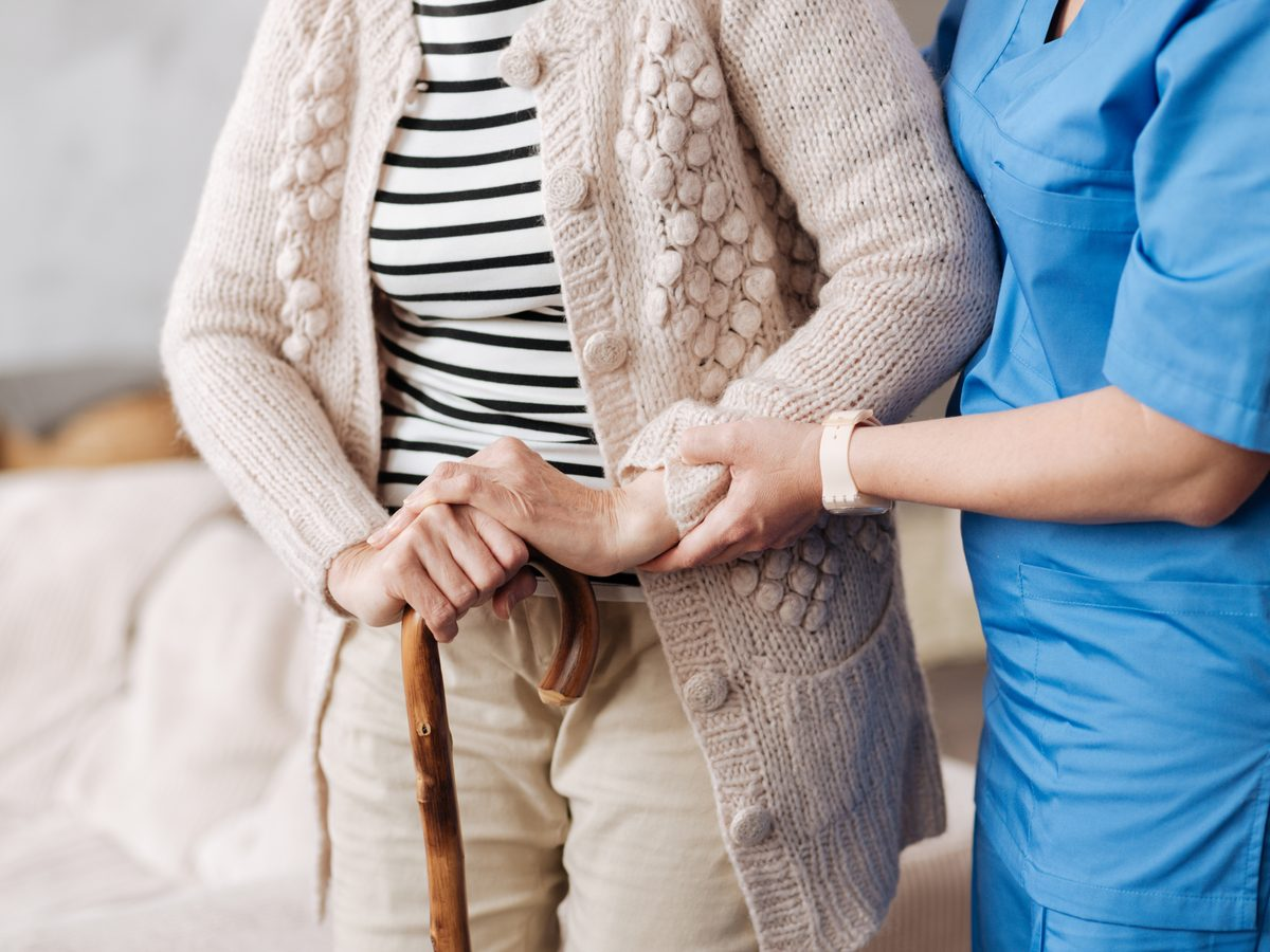 Nurse helping senior woman stand at her home