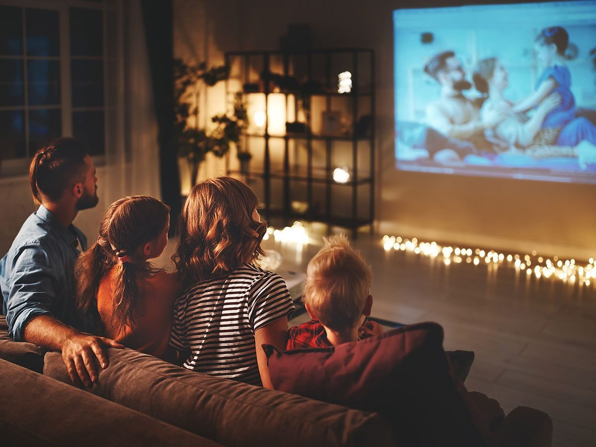 Family watching movie in home theatre.