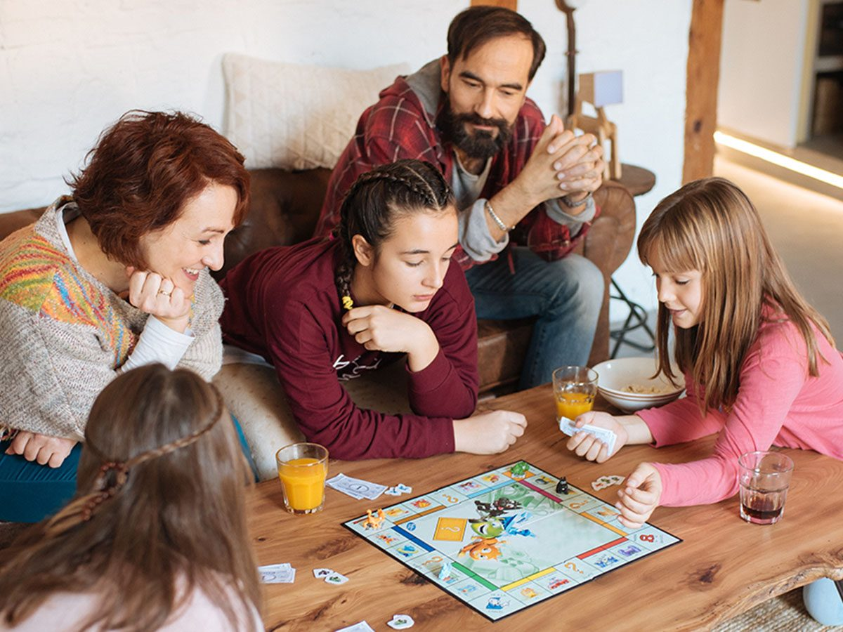 Family playing a game of monopoly.