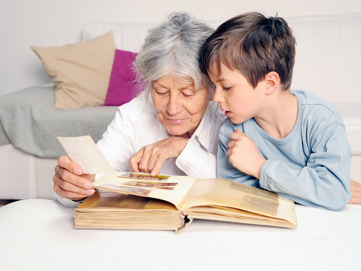 Grandma looking at old photos with grandson.